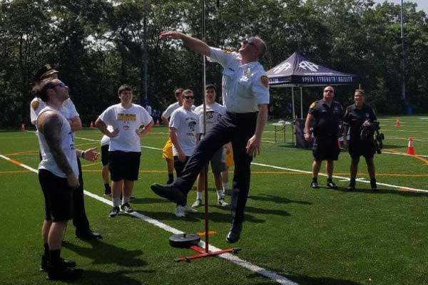 officer jumping to test height while young adults watch