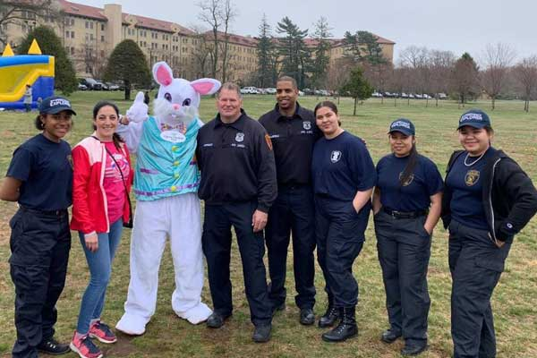 police with young adults and person in a rabbit costume posing for camera