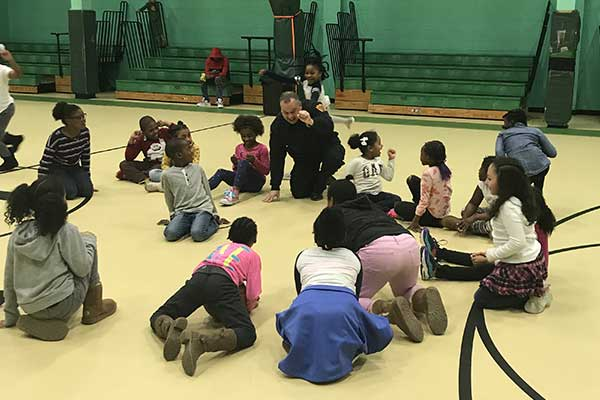 young children sit in a circle on a school gym floor, in the middle an officer speaks